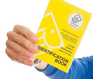 A person holding a yellow ADUK ID booklet